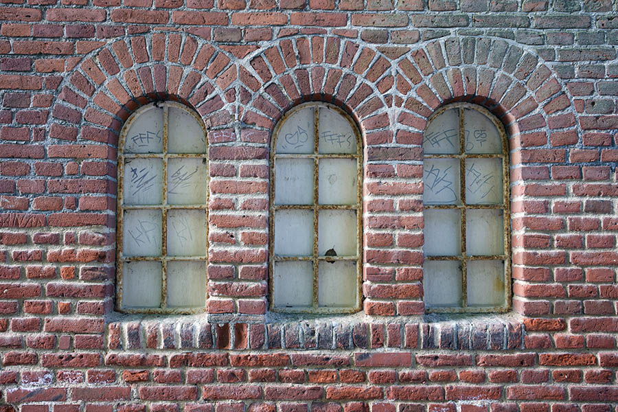 Photo 25287: Facade with three worn, formed, white metal windows in a red brick wall