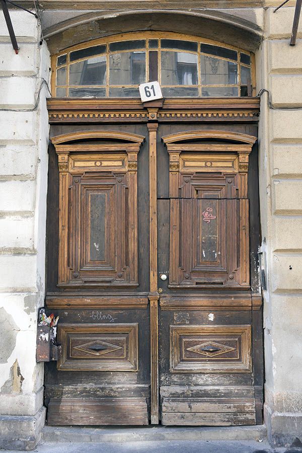 Photo 26088: Worn, panelled, brown and oiled, carved double door with fan light and minor door